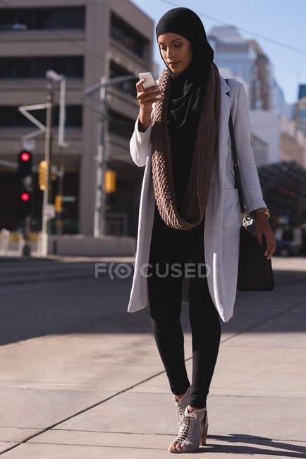 Bella donna hijab utilizzando il telefono cellulare in città — Foto stock