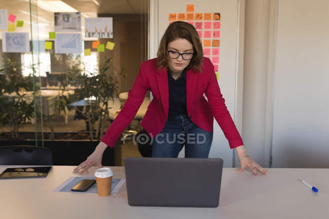 Femmina business executive guardando computer portatile in ufficio — Foto stock