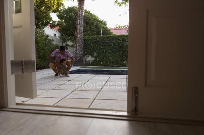 Батько і син грає поза домом в саду — стокове фото