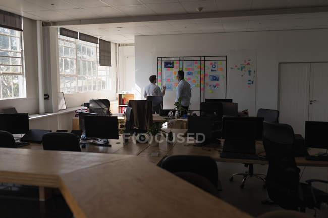 Dirigenti maschili discutono su appiccicose note in ufficio — Foto stock