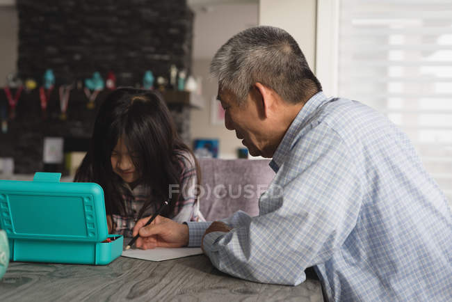 Grandfather and granddaughter drawing sketch on dining table at home — Stock Photo