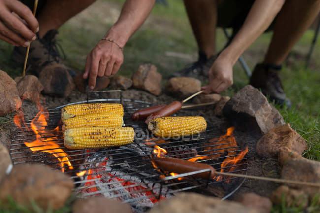Close-up of men roasting sausage and corn on campfire at campsite — Stock Photo