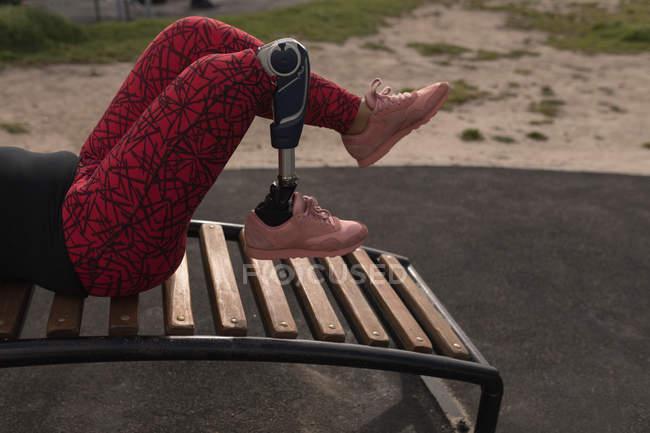 Baixa seção de mulher com deficiência exercendo no jardim — Fotografia de Stock