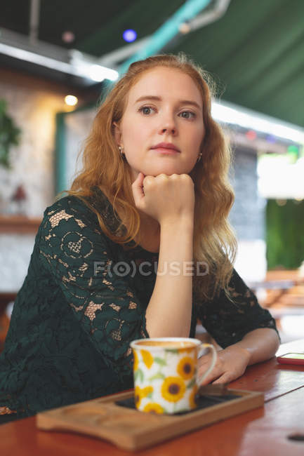 Thoughtful redhead woman relaxing in cafe — Stock Photo