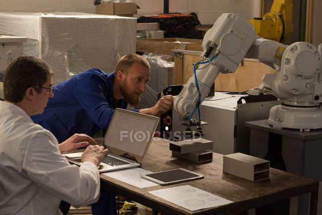 Инженеры-роботы осматривают роботизированную машину на складе — стоковое фото