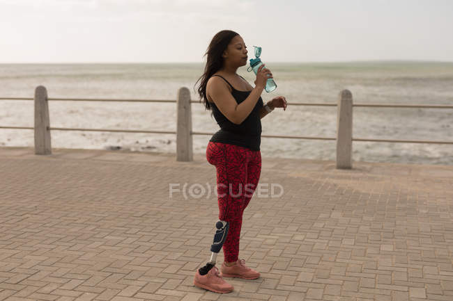 Side view of disabled woman drinking water on promenade — Stock Photo