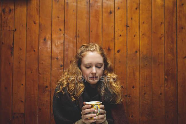 Рыжая женщина держит кофейную кружку в кафе — стоковое фото