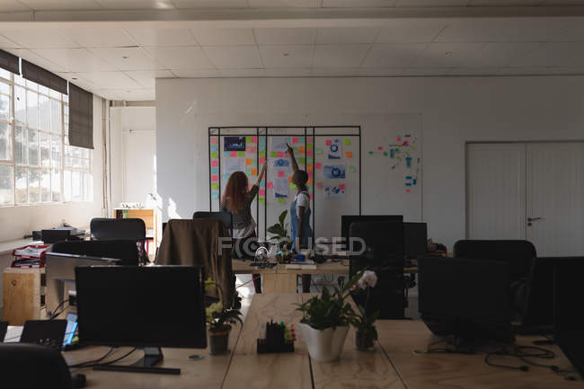 Female executives discussing over sticky notes in office — Stock Photo