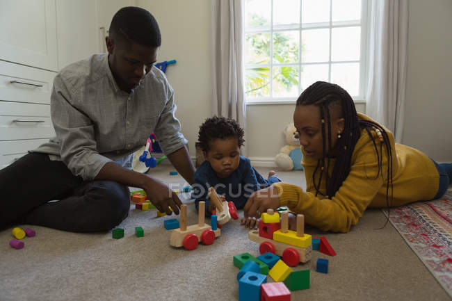 Family playing with a child in a living room at home — Stock Photo