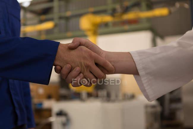 Макро з робототехнічних інженерів потискують один одному руки один з одним — стокове фото