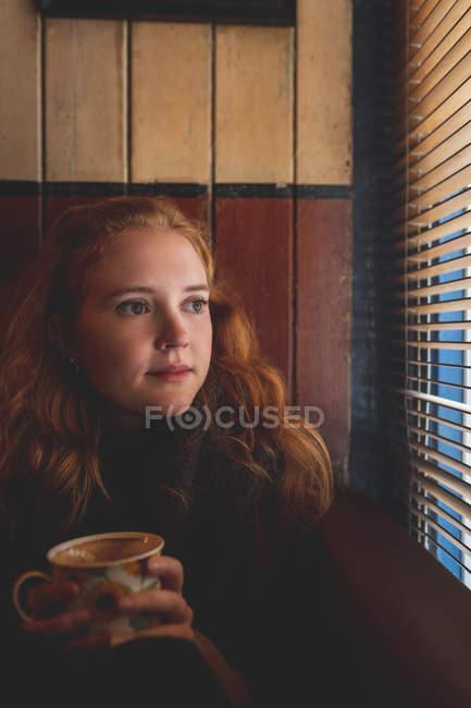 Вдумчивый Рыжая женщина, глядя через окно слепой в кафе — стоковое фото