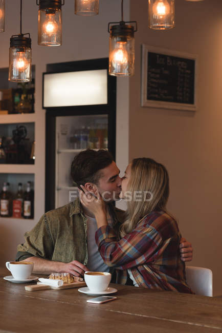 Romantic couple kissing each other in cafe — Stock Photo