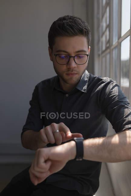 Maschio esecutivo utilizzando smartwatch in ufficio — Foto stock