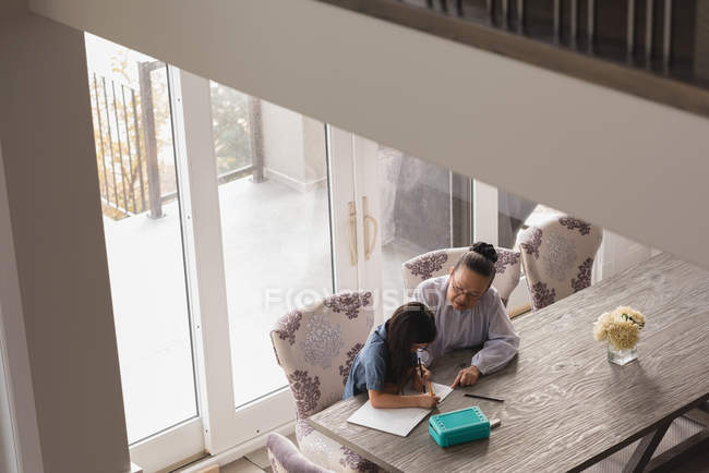 Grandmother and granddaughter drawing sketch on table at home — Stock Photo