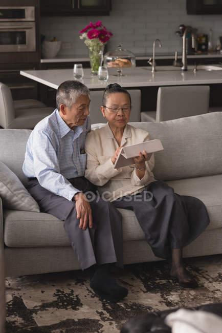 Couple de personnes âgées discutant sur une tablette numérique sur le canapé dans le salon à la maison — Photo de stock