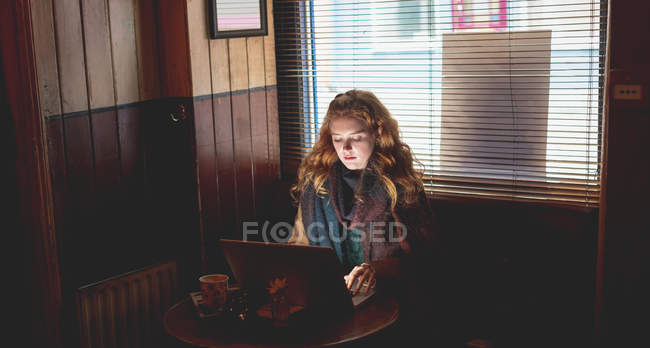 Redhead woman using laptop in cafe — Stock Photo