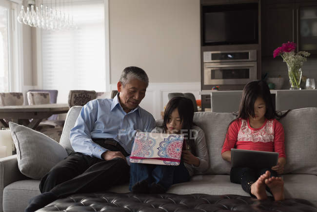 Grandfather and granddaughters using digital tablet on sofa in living room at home — Stock Photo