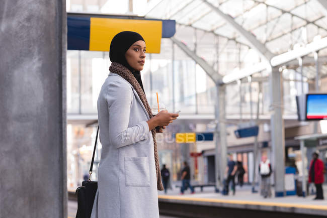 Hijab woman waiting for train while using mobile phone at railway station — Stock Photo