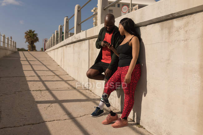 Couple discussing on mobile phone on a sunny day — Stock Photo