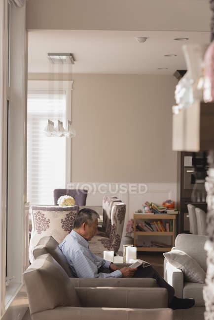 Uomo anziano che utilizza tablet digitale in soggiorno a casa — Foto stock