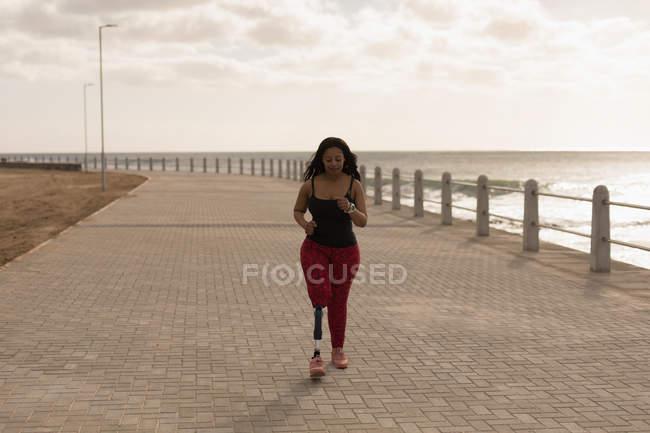 Beautiful disabled woman walking on promenade — Stock Photo