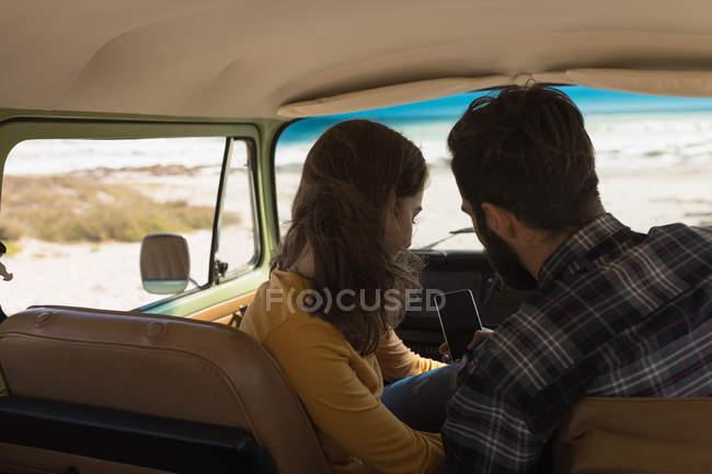Pareja usando teléfono móvil en vehículo en viaje por carretera - foto de stock