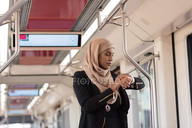Hijab woman using smart watch while travelling in train — Stock Photo