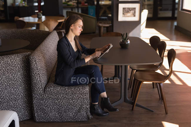 Businesswoman using digital tablet in cafeteria at office — Stock Photo