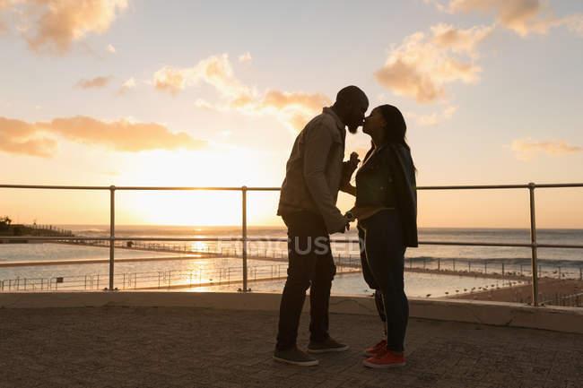 Romántica pareja besándose en el paseo marítimo - foto de stock