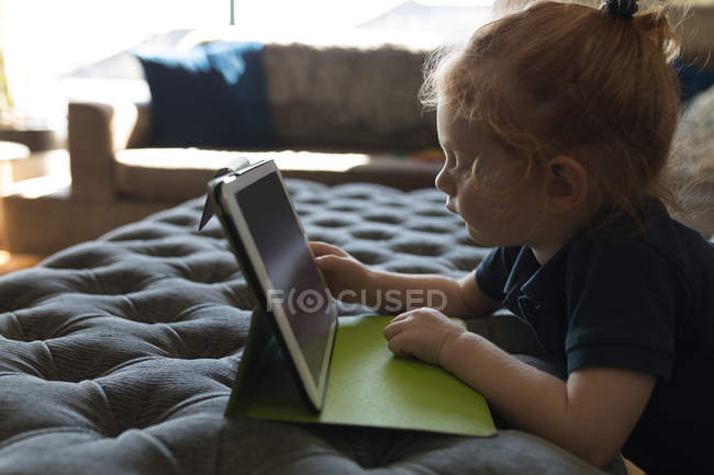 Vista laterale della ragazza utilizzando tablet digitale in soggiorno a casa — Foto stock