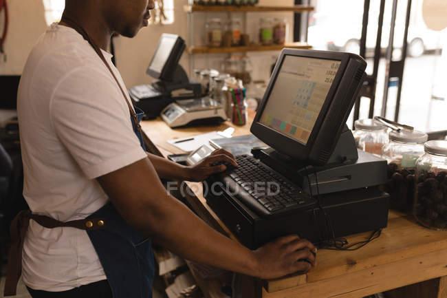 Мужской персонал работает за компьютером на прилавке в супермаркете — стоковое фото