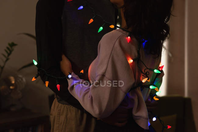 Romantic couple wrapped in fairy lights embracing each other at home — Stock Photo