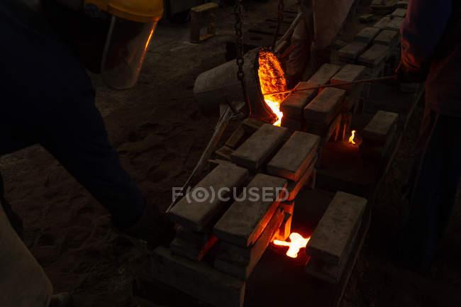Arbeiter gießt geschmolzenes Metall aus Kolben in Formen in Gießerei — Stockfoto