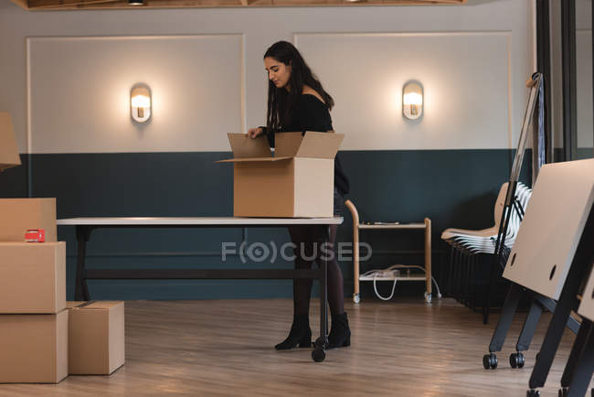 Businesswoman unboxing cardboard box in office — Stock Photo