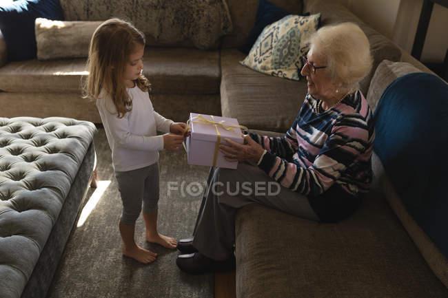 Enkelin schenkt Großmutter im heimischen Wohnzimmer — Stockfoto