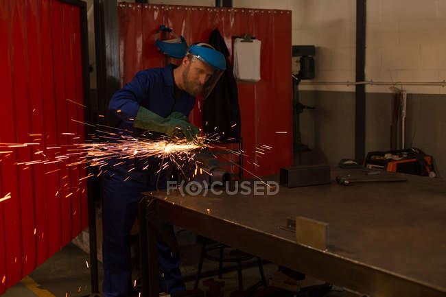 Робототехнические инженеров, с помощью шлифовальной машины на складе — стоковое фото