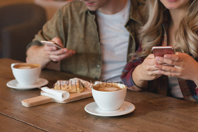 Close-up of couple using mobile phone in cafe — Stock Photo