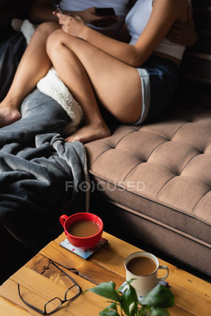 Low section of couple using mobile phone on sofa in living room at home — Stock Photo