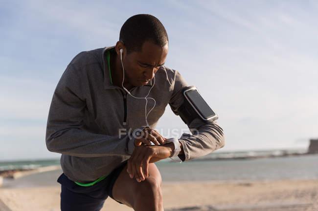 Athlète masculin en vérifiant sa smartwatch pendant l'exercice près de la plage — Photo de stock