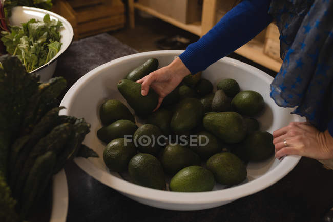 Mid section of woman picking avocado from basket in supermarket — Stock Photo