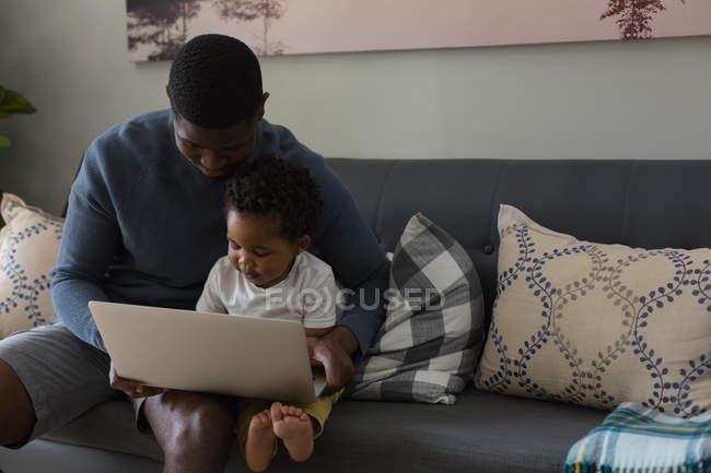 Отец и сын используют ноутбук в гостиной на дому — стоковое фото