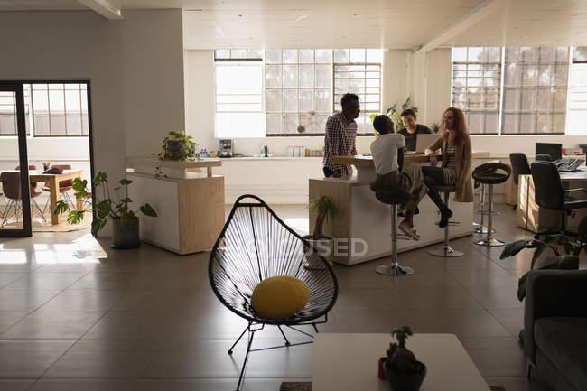 Giovani dirigenti che parlano tra loro in ufficio — Foto stock