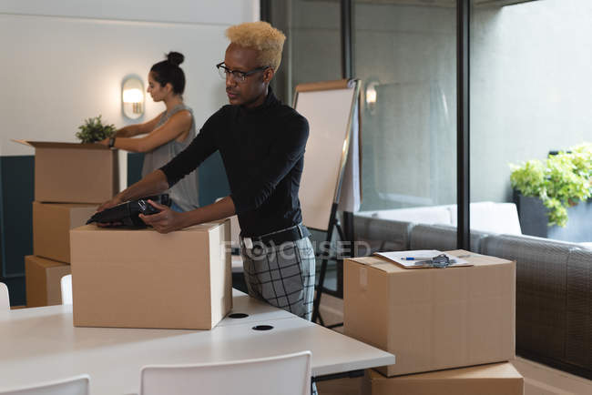 Businessman unboxing cardboard box in office — Stock Photo
