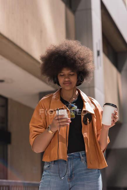 Женщина пьет кофе во время прослушивания музыки на мобильном телефоне в городе — стоковое фото