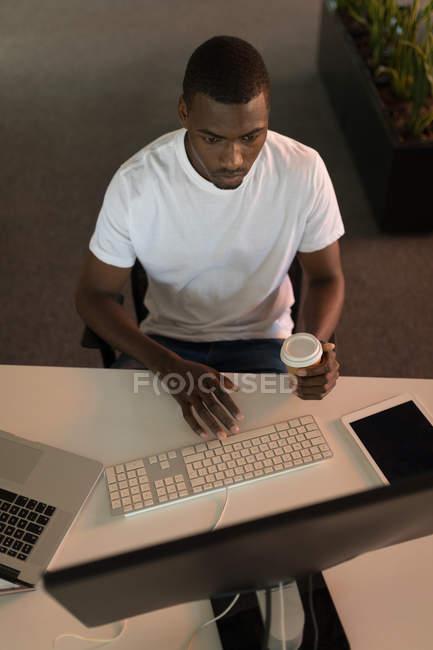 Business executive che lavora alla scrivania mentre prende un caffè in ufficio — Foto stock