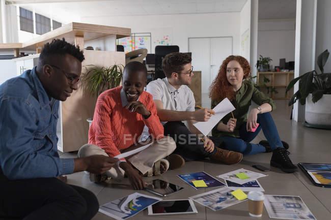 Jóvenes ejecutivos que trabajan en el piso de la oficina - foto de stock