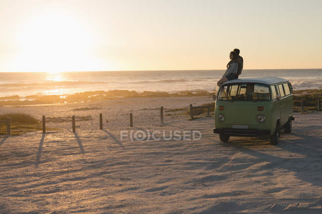Couple sitting top of the van during sunset on beach — Stock Photo