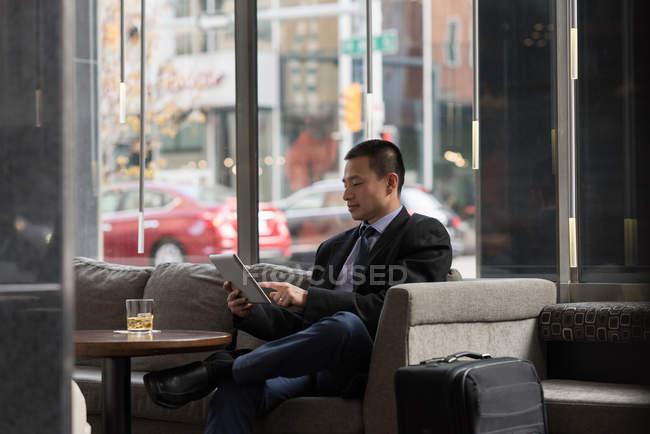 Empresario usando tableta digital en sofá en hotel - foto de stock