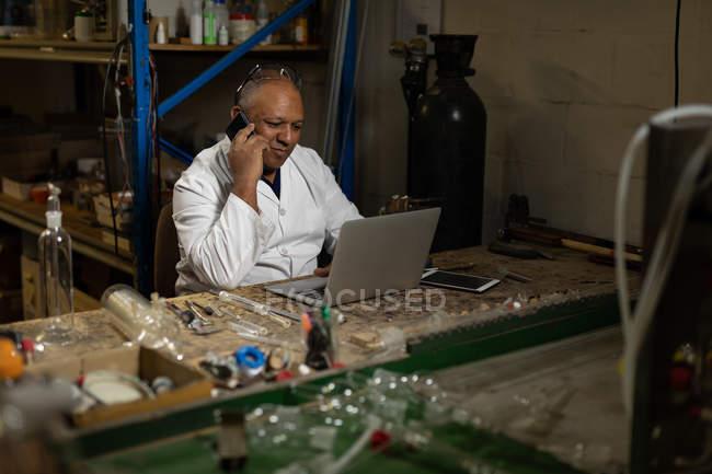 Arbeiter telefoniert mit Laptop in Glasfabrik — Stockfoto