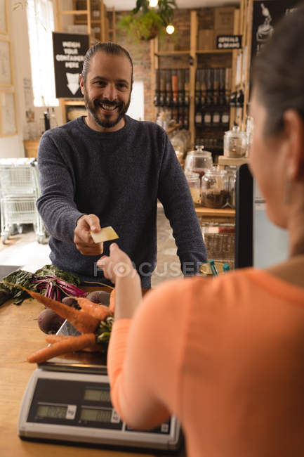 Customer making payment with credit card at counter in supermarket — Stock Photo